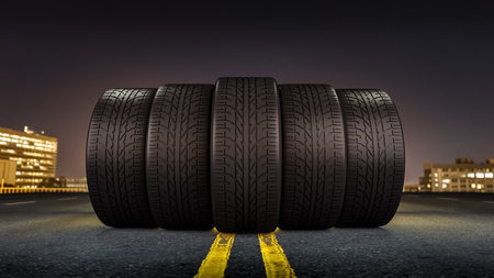 Five tires rolling on a street in a city at night. Imagens