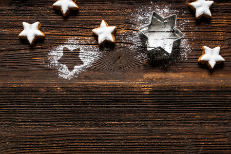 Fresh cinnamon star shaped cookies with frosting on wooden table.