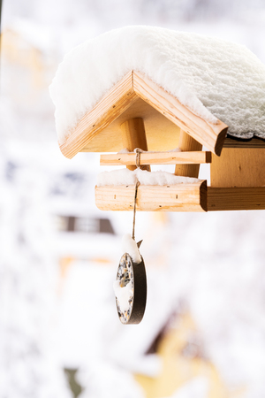 Snow covered wooden birdfeeder in winter. Stock Photo