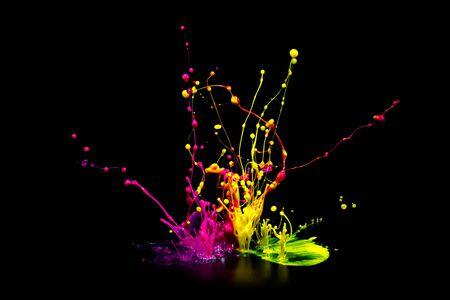 Colorful paint splashing on audio speaker isolated on black background