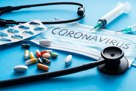Protective face mask,pills, syringes and Stethoscope on blue background, against Novel coronavirus 2019-nCoV or  coronavirus . Hygiene and Healthcare concept