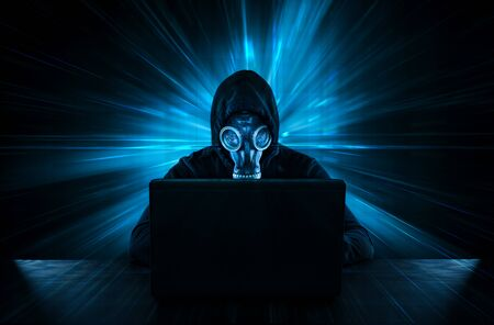 Male thief in gas mask stealing data from computer