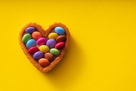 Colorful Candy Buttons on Heart shaped cake on yellow Background - Birthday concept
