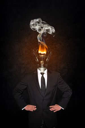 Overworked burnout business man standing headless with broken Bulb instead of his head. Symbolic Image - Stress Concept Imagens