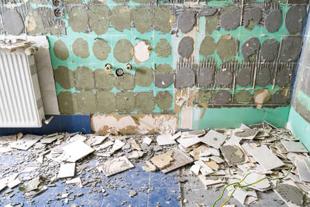 Pile of ceramic tiles remains after bathroom renovation prepared to be thrown into the trash