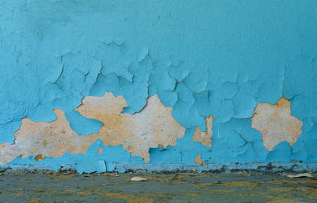 The old cracked blue paint on a wall surface with messy ground