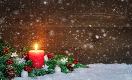 Christmas or Advent wood background with burning red candle on snow and snowflakes, decorated with fir branches and ornaments. Copy space Imagens