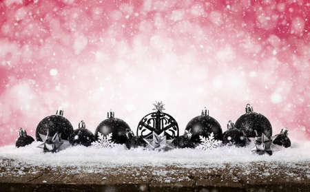 Red Christmas Background - Decorated Black Balls On Snow with snowflakes and stars on wooden desk.