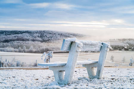 Winter mountains landscape and wooden iced bench in the morning
