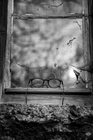 Vintage reading glasses lie on window sill against the window reflection of clouds - Black and White