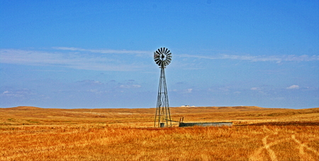 Windmill pumping water in Fairburn South Dakota between the east side of the Black Hills Stock Photo