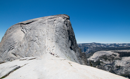 Cables with climbers on Half Dome as seen from the Sub Dome in Yosemite National Park in California United States