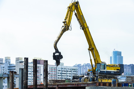 KAOHSIUNG, TAIWAN -- JUNE 14, 2016: An excavator drives a pile into the river bed as construction of a new bridge across the Love River continues.