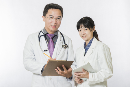 crossing arms: Cheerful doctors posing together crossing arms on white background