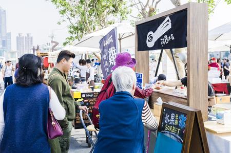 KAOHSIUNG, TAIWAN - FEBRUARY 18, 2018: Tourists watch merchandise in the pedestrian street of the Art SAR.