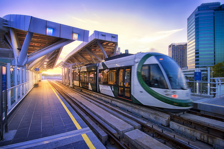Kaohsiung, Taiwan -- March 2, 2018: A train of the new light rail system pulls into the Love Pier station at sunset time. Editorial