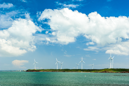 Penghu Taiwan The windmills in the island of wind turbines and the rocks in the middle of reefs flow to the ocean, reflecting the beautiful pictures of blue sky and white clouds.