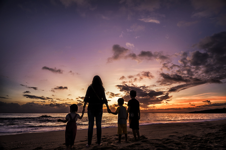 Silhouette of family standing in a multicolored sunset.