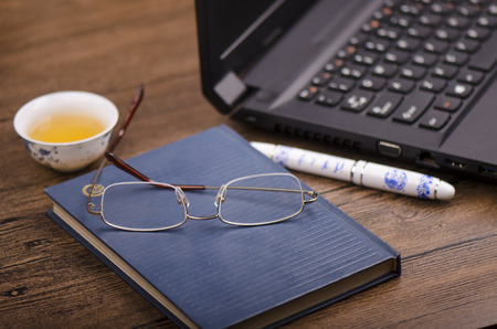 enterprising: Stationery and laptop on a wooden table Editorial