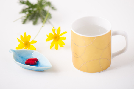 Pills and a cup of water on white background