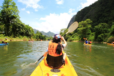 The young woman kayaking in Song River that surrounded by mountains