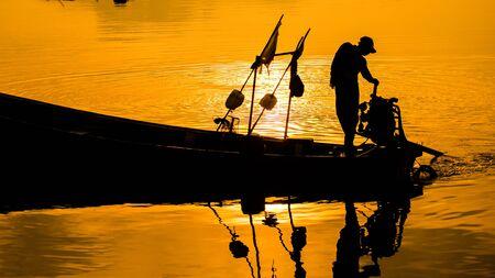 Silhouette of fishing boat and fisherman on sunset,Samchong-tai, Phangnga, Thailand,Fishing village boat ,net and sunrise.Thailand Zdjęcie Seryjne
