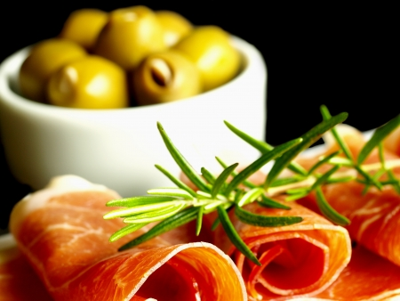 ham of Spain Jamon Serrano decorated with rosemary and olives Stock Photo