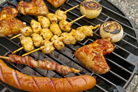 barbecue with chicken wings,Bratwurst, meat skewer and ham photo