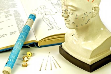 acupuntura china: Las agujas de acupuntura, el modelo de la cabeza, los libros de texto y rollo de moxa