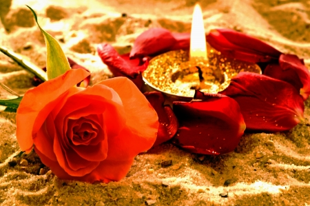 tealight: Tea-light with rose on a beach Stock Photo