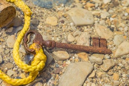 beachcombing: old key in the sea Stock Photo