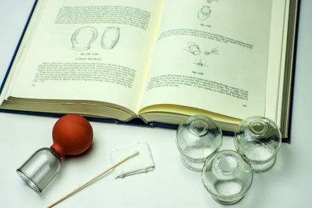 Cupping glasses with textbook Stockfoto
