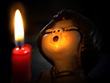 angel sings in candle-light photo