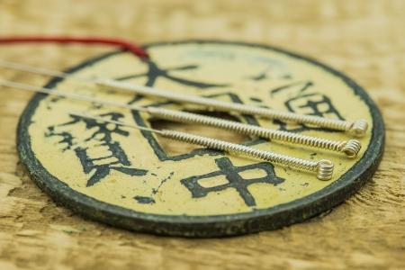 Akupunkturnadeln mit antiken chinesischen Münzen Lizenzfreie Bilder