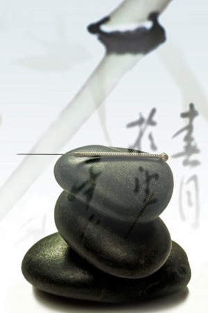 warming therapy: Acupuncture needle on stone pyramid
