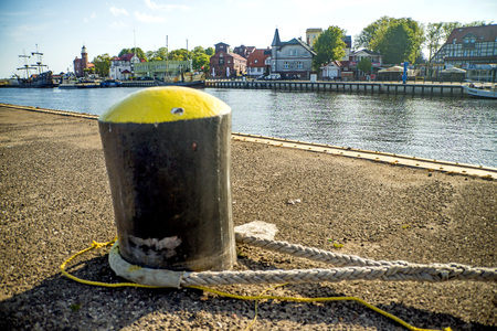 fixed line: bollard in a seaport with sailing ship and lighthouse Stock Photo