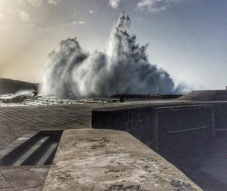 ocea: big wave breaks at a mole Stock Photo