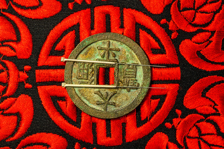acupuncture needles on Chinese coin and symbol for immortality Stock Photo
