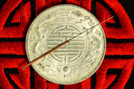 acupuncture needle on Chinese coin and symbol for immortality