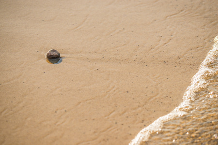 single stone on a sand beach with surf