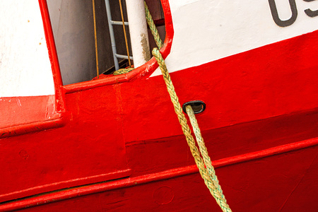 Mooring line of a trawler on a red ship hull Standard-Bild - 119602909