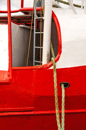 Mooring line of a trawler on a red ship hull Standard-Bild - 119602910