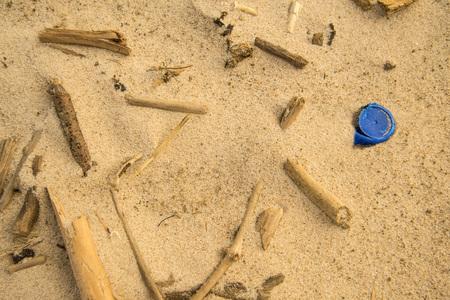 driftwood and plastic lid on a beach Standard-Bild - 119602912