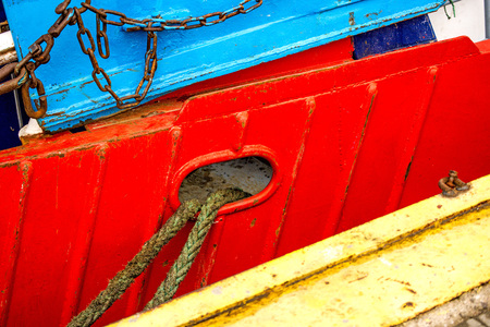 Mooring line of a trawler on a red ship hull