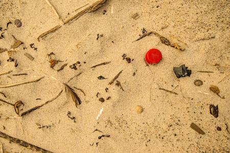 plastic waste on a beach, red lid Standard-Bild - 119602938