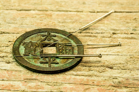 acupuncture needles on antique Chinese coin Standard-Bild - 119602945