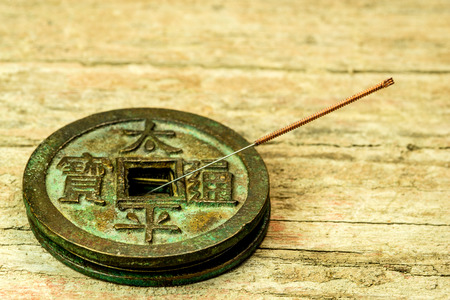 acupuncture needle on antique Chinese coin Standard-Bild - 119602969