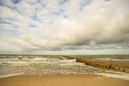 lonesome beach of the Baltic Sea with cloudy sky and surf Standard-Bild - 119602972