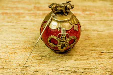 acupuncture needle on antique Chinese paperweight Standard-Bild - 119603042