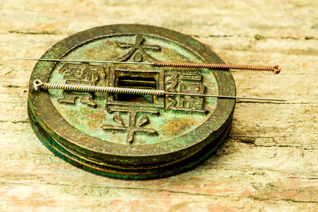 acupuncture needles on antique Chinese coin Standard-Bild - 119603056